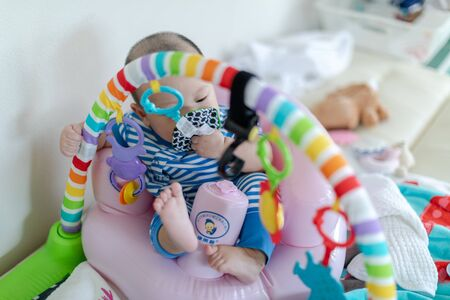 Baby with toy in mouth on play gym at home