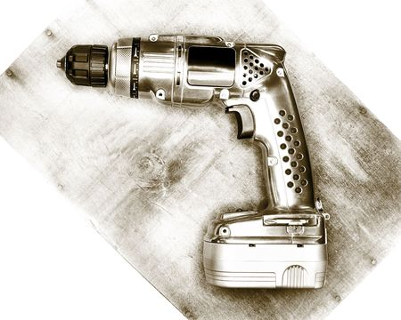 Classic looking cordless drill, laying on a piece of wood. photo