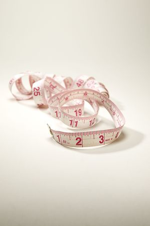 taylor: Fabric tapemeasure on a seamless background.