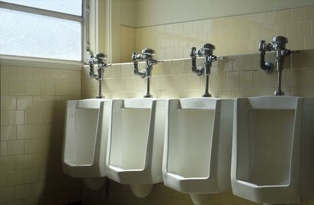 Four urinals in a row, near a window in a commercial building. Stock Photo