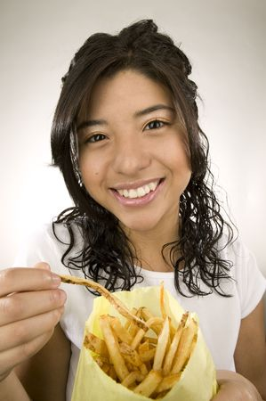 Portrait of a teenage Latina with fries.