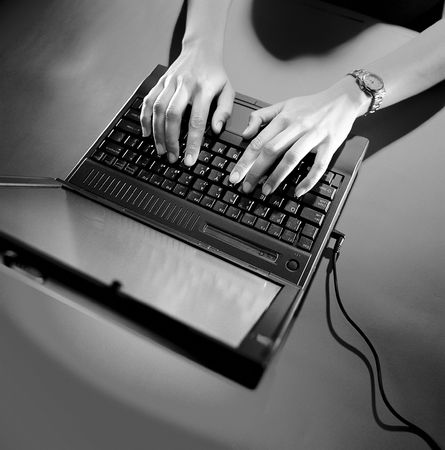 old notebook: Woman using an old notebook computer with the power cord attached. Stock Photo