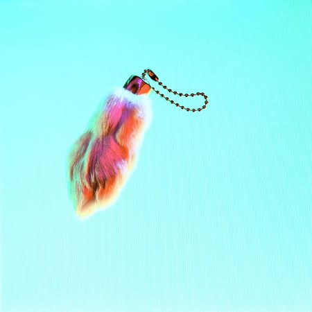 goodluck: Rabbits foot keychan on a bright textured background.