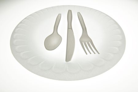 Plastic cutlery and a plate on a white background.