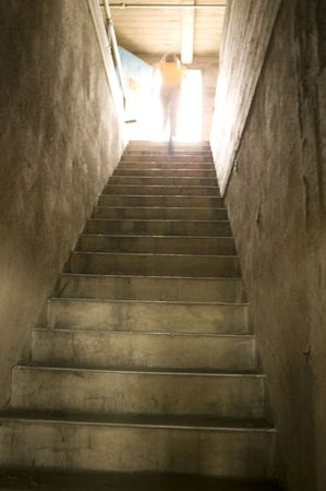 Man running to the top of old concrete stairwell leading to roof access with daylight at top. Stock fotó