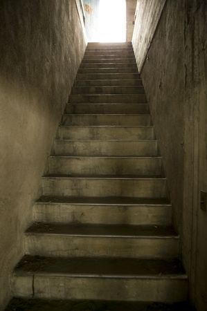 Old concrete stairwell leading to roof access with daylight at top. Stock Photo