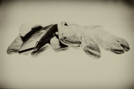 Old leather gloves and a utility knife. I never did like thse gloves much, but I like the picture. Reklamní fotografie