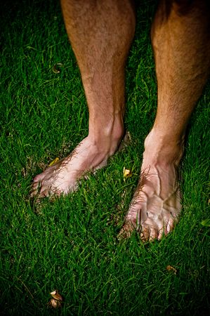 A man standing in the grass in his bare feet on a summer day.