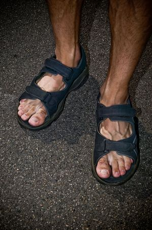 A man standing on the sidewalk in his sandals on a summer day.