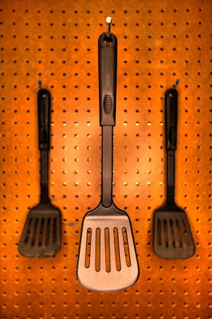 Professional cooking utensils in a restaurant kitchen, hanging o a pegboard wall.
