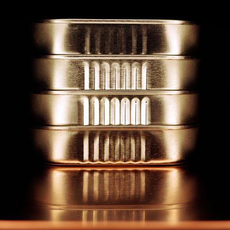 A small stack of sardine tins on a reflective background