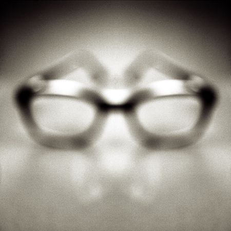 Horn rimmed safety glasses out of focus on a clean background. Imagens
