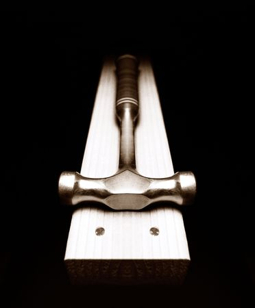 A claw hammer on a 2 x 4 with two nails set flat.