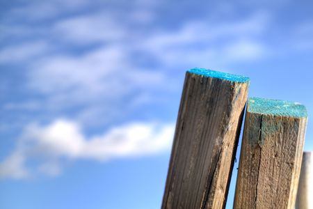 A couple of posts leaning against a fence, with a blue sky in the background. Stock Photo