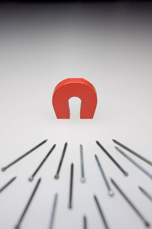 A small magnet with  a stack of brads demonstrating attraction Stock Photo