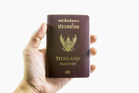 consulate: Thailand passport in hand isolated on a white background