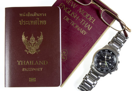 Dictionary Thailand with watches and passport isolated on white background photo