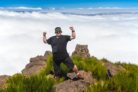 Obese man standing at top of the mountain over the clouds. If you want, you can achieve even hard and tough goal. All you need is desire and strong will. Even fat people can achieve their own tops.