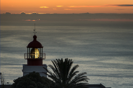 Lighthouse with dome and moving light mirror at the shore of Madeira. Cloudy sunset starting blue hour