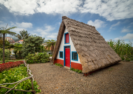Traditional house of Madeira. Thatched roof in characteristic triangle shape. House is surrounded by intense flowers from nearby garden