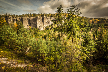 Tall pines in autumn mountains scenery. Steep ridges of Skalni Mesto in Czech National Park. Beautiful, colorful fall trees painted in yellow, gold, red and green. Dramatic cloudy sky adds climate to the scene