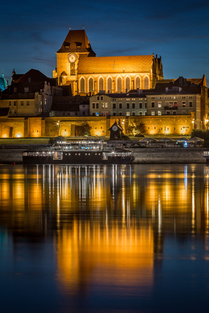 StJohns Baptist and St Johns Evangelist cathedral reflected in Vistula river at calm evening, Torun, Poland