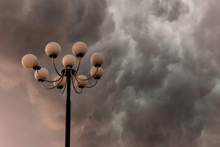 Lightning flashes stormy clouds over big, glorious street lamp