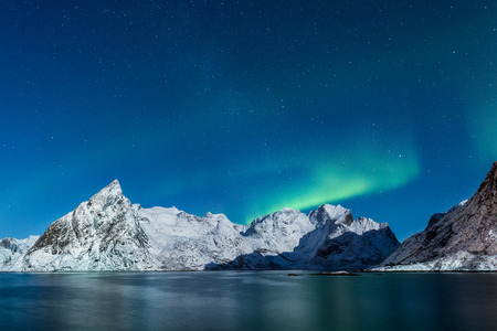 northern light: Northern lights over winter, snow covered mountains of Lofoten, Norway with starry sky