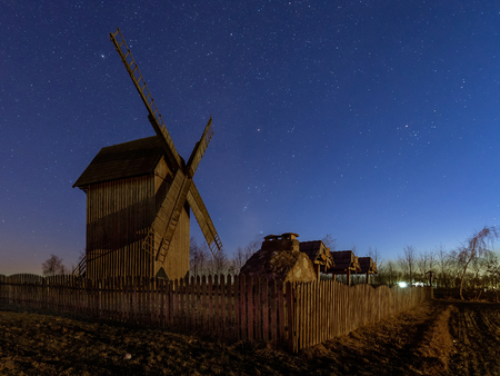 Old wooden windmill at coutryside in the night. Last moments to see winter star constellations as Orion. Clear sky and firmament full of stars
