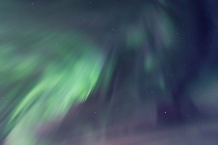 Sky brighten by dynamic aurora borealis. Green and purple northern lights dancing on the starry sky