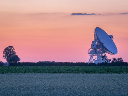 Pastel colors on the sky during summer sunset over radiotelescope antenna