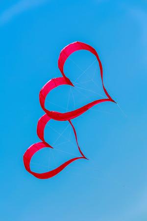 fling: heart kite fling on blue sky Stock Photo