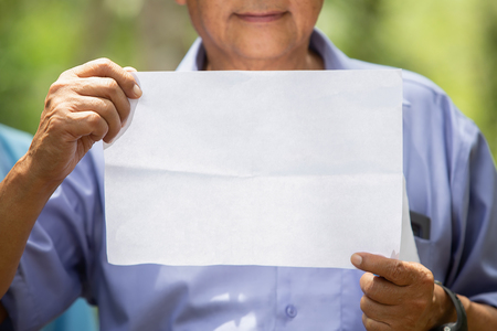the elder man hold a white paper in his hand Stock Photo