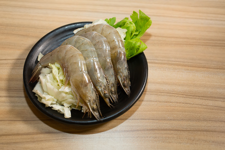 shrimp in black plate on wooden table background