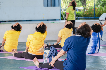 Elderly in a yoga exercise posture In order to have a good body image, therefore, must exercise and train by experts Stock Photo