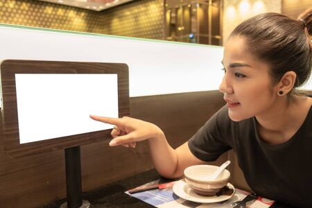 Beautiful woman Asians are pointing their fingers on the monitor screen to order food in the restaurant.