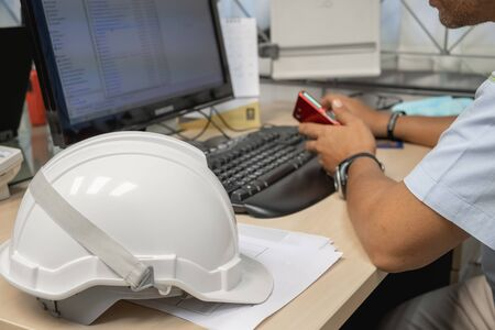 White industrial safety helmets were placed in the office, on a table where employees were working. And hold the phone in the hand as the background 写真素材