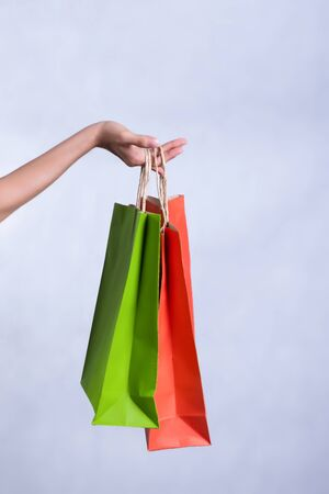 Shopping bags with red and green colors A woman's hand On a white background 写真素材