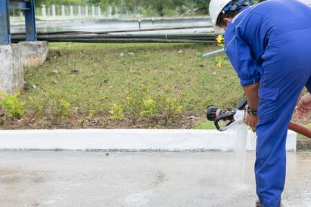 A worker in a blue factory suit Wear a white helmet Installing fire hose There is a grass background
