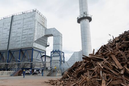 Picture of a thermal power plant that has people working and firewood to make fuel.