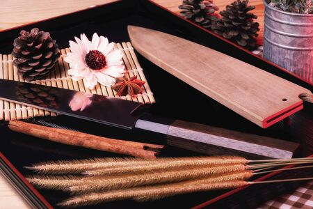 Japanese knives are placed on a black wooden tray on a brown wooden table. Close to beautiful flowers
