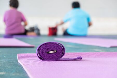 The pink yoga mat has a purple rope on top. The carpet is laid on the green concrete floor. There are elderly women sitting in the background. focus to the rope.
