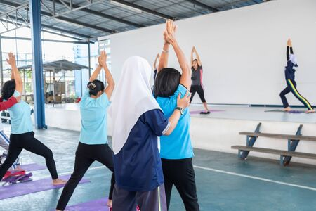 Posture of exercise with yoga There are participants of all ages, both young and old. With a Muslim female trainer closely