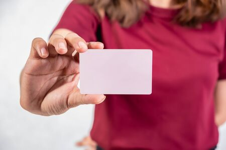 Girl wearing red shirt While holding a credit card in the hand With a white background