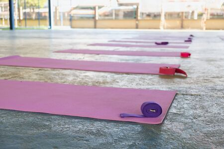 The pink yoga mat has a purple rope on top. The carpet is laid on the green concrete floor.