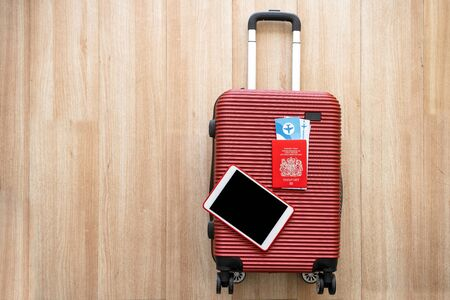 Equipment for company employees preparing to travel or work abroad,tablet and passport Placed on a red suitcase Getting ready for travel