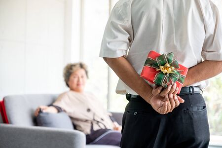 senior asia man hiding present for his wife behind back on valentineday .  Senior couple asia celebrating anniversaryday. senior woman smile with husban for surprise birthday or new year gift.