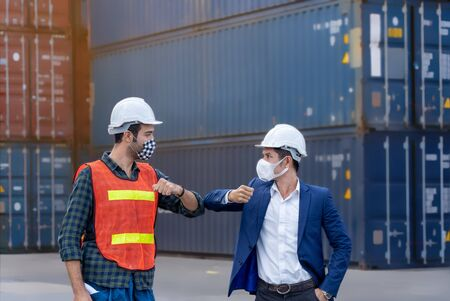 New normal concept,Engineer worker greeted by bumping elbow for distance between people wearing mask and helmet in the factory or container yard Prevent accident from work or dust and Coronavirus.
