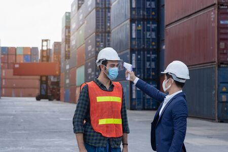 New normal concept,Engineer check the staff integrity by measuring the temperature,wear mask and helmet before working in factory or warehouse area Prevent accident from work or dust and Coronavirus