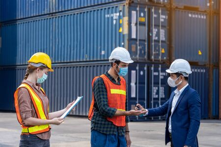 Engineer assistant inspector protect body by wearing mask,helmet and wash hand with alcohol Before entering warehouse or factory Prevent accident from work dust and Coronavirus. New normal concept Stockfoto